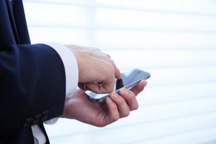 会社の窓際で携帯電話を操作する男性の写真素材 [FYI02448553]