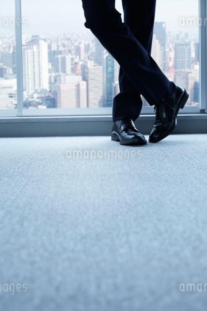 窓辺に立つ男性の足元と床の写真素材 [FYI02448558]
