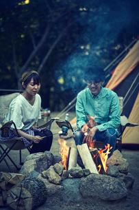 テントの前でたき火をする二人の写真素材 [FYI02448561]