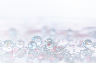 反射する板に置かれた複数のガラス粒とガラス玉の写真素材 [FYI02448722]