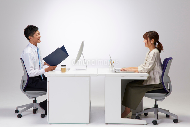 向かい合わせのデスクで仕事をする男女の写真素材 [FYI02448763]