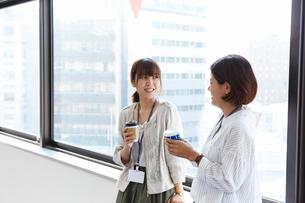オフィスの窓際で会話するOLの写真素材 [FYI02448810]