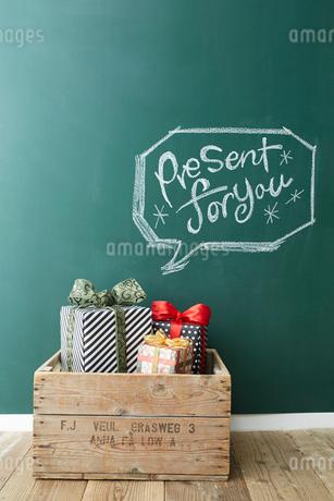 木の箱に入った三つのプレゼントボックスと黒板に描かれた吹き出しの写真素材 [FYI02449373]
