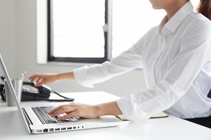 オフィスでノートパソコンをしながら受話器に手をかける女性の写真素材 [FYI02449658]