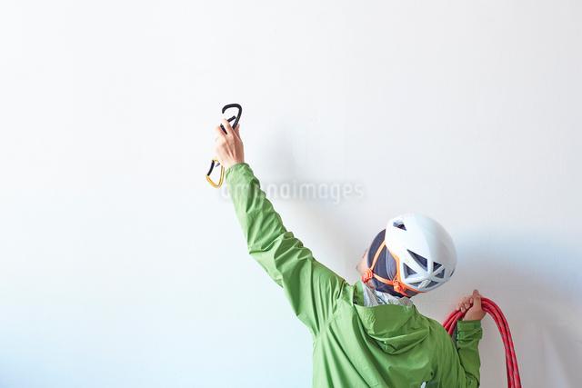 白い壁の前でロープを持ち体を伸ばしてカラビナを引っ掛けようとする登山者の写真素材 [FYI02449686]
