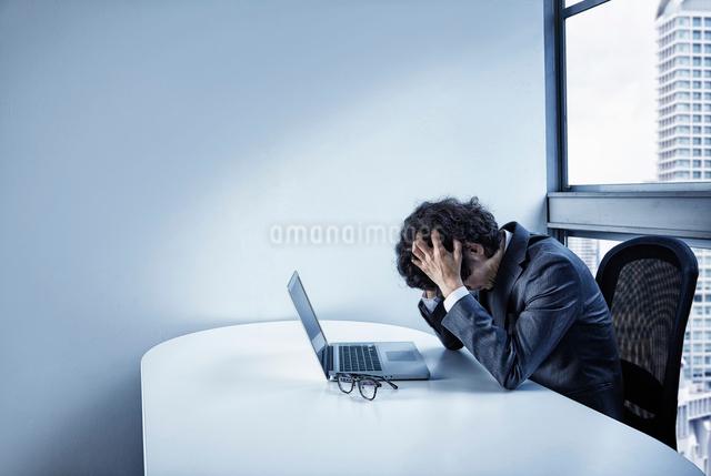 会社のデスクで頭を悩ませるビジネスマンの写真素材 [FYI02449693]