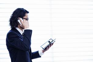 会社の窓際で手帳を見ながら電話をする男性の写真素材 [FYI02450090]