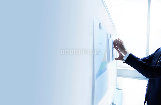 ホワイトボードに書類を貼る男性の手元の写真素材 [FYI02450181]