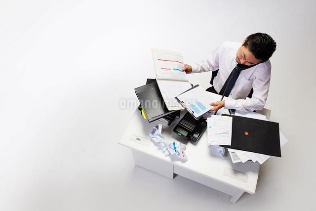 仕事が山積みのデスクで電話をするサラリーマンの写真素材 [FYI02450209]