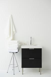 シルバーのスツールの上に畳まれたタオルと洗面台の写真素材 [FYI02450366]