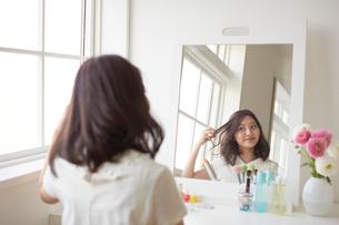 鏡に向かい髪の毛を手入れする若い女性の写真素材 [FYI02450422]