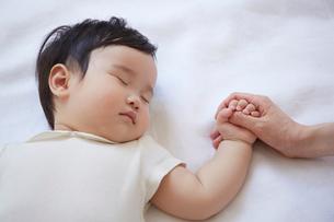 寝ている赤ちゃんと手をつないでいるお母さんの手の写真素材 [FYI02450528]