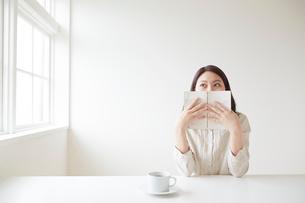 本で口元を隠す若い女性の写真素材 [FYI02450542]