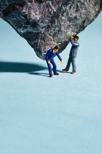 重石を支える人とそれを助ける人の写真素材 [FYI02450637]