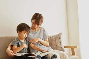 ソファーで図鑑を見る親子の写真素材 [FYI02451256]