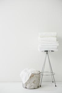 白い空間に置かれた畳まれたタオルと洗濯物の写真素材 [FYI02451318]