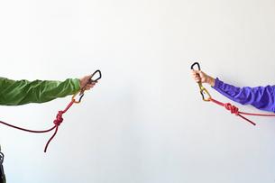 白い壁の前でロープを持ちカラビナを引っ掛けようとする2人の登山者の写真素材 [FYI02451325]
