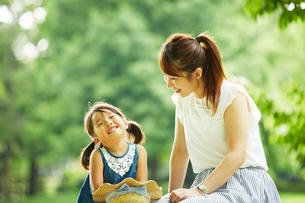 公園内で座って話をするお母さんと女の子の写真素材 [FYI02451397]
