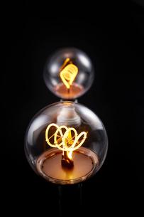 黒い背景の上にあるふたつの電球の写真素材 [FYI02451495]