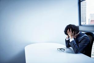 会社のデスクで頭を悩ませるビジネスマンの写真素材 [FYI02451564]