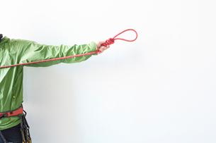 白い壁の前で結んだロープ持って引っ張る登山者の写真素材 [FYI02451580]