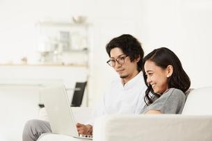 リビングのソファーでパソコンを見ている男女の写真素材 [FYI02451636]