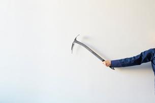 白い壁の前でピッケルを構える人の写真素材 [FYI02451695]