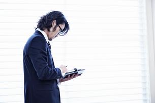 会社の窓際で手帳を見る男性の写真素材 [FYI02451699]