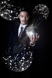光の粒から出た線が手のひらに集まったビジネスマンの写真素材 [FYI02451710]