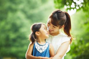 公園内でお母さんの膝の上に座って見つめ合う女の子の写真素材 [FYI02451730]
