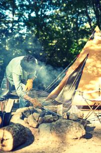 テントの前で火を起こす男性の写真素材 [FYI02451731]