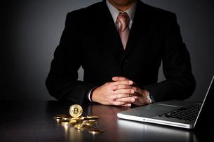 パソコンでビットコインのビジネスをするスーツを着た男性の写真素材 [FYI02451792]