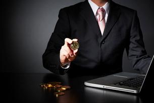 パソコンでビットコインのビジネスをするスーツを着た男性の写真素材 [FYI02451845]