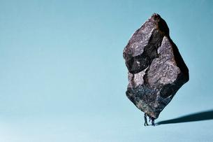 重石を支える人とそれを助ける人の写真素材 [FYI02451903]
