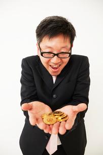 ビットコインのビジネスに成功したスーツを着た男性の写真素材 [FYI02451904]