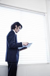 会社の窓際で資料を見る男性の写真素材 [FYI02451916]