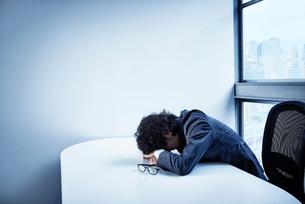 会社のデスクで頭を悩ませるビジネスマンの写真素材 [FYI02452001]