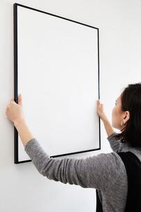 壁に額を掛ける女性の写真素材 [FYI02452020]