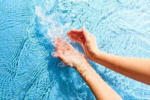 水をすくいあげる女性の手元の写真素材 [FYI02452033]