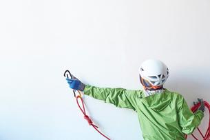 白い壁の前でロープを持ち体を伸ばしてカラビナを引っ掛けようとする登山者の写真素材 [FYI02452053]