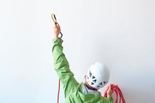 白い壁の前でロープを持ちカラビナを引っ掛けようとする登山者の写真素材 [FYI02452058]