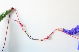 白い壁の前でカラビナがかかったロープを引っ張る2人の登山者の写真素材 [FYI02452067]