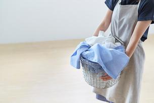 白い壁の前で籠いっぱいの洗濯ものを抱える女性の写真素材 [FYI02452135]