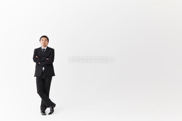 腕組みをし一人で立つサラリーマンの写真素材 [FYI02452323]