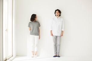 壁前に立つ男女二人の写真素材 [FYI02452334]