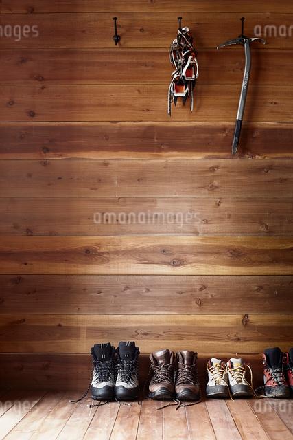 山小屋の中に置かれた紐をほどいた4足のトレッキングシューズと壁に掛けられた登山用品の写真素材 [FYI02452337]