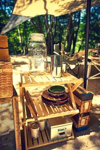 森に貼られたタープとキャンプ用品の写真素材 [FYI02452340]