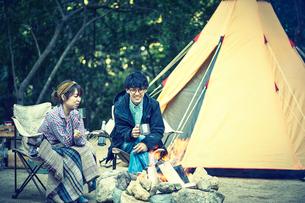 テントの前でたき火をする二人の写真素材 [FYI02452343]