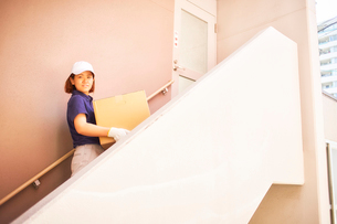 マンションの階段で立つ作業服の女性の写真素材 [FYI02452363]