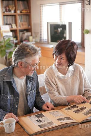 古いアルバムを見るミドル夫婦の写真素材 [FYI02453732]